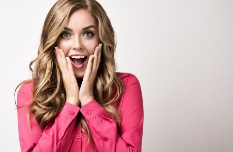 美丽的金发美女在一张惊讶的脸粉红色外套
