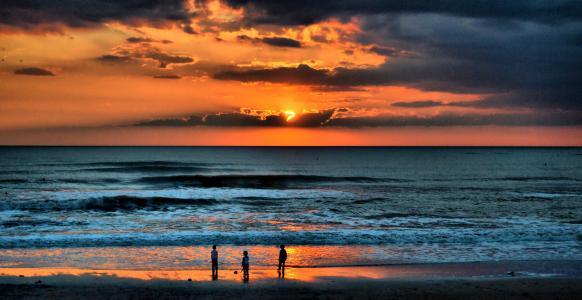 在西班牙海滩上散步的人