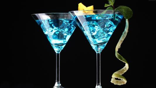孟买与冰,石灰和杜松子酒在黑色背景上的鸡尾酒