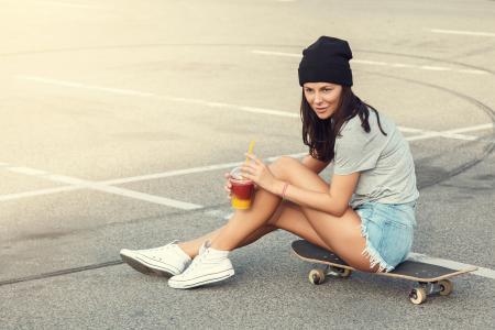 运动女孩坐在滑板上
