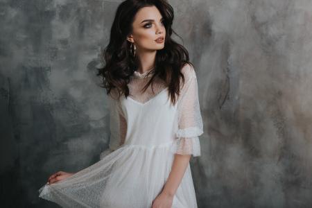 美丽的浪漫女孩黑发在白色的裙子