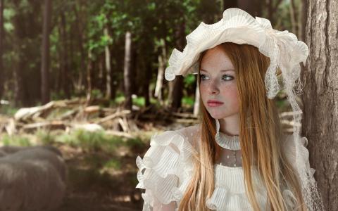 戴着白帽子的雀斑女孩站在树旁