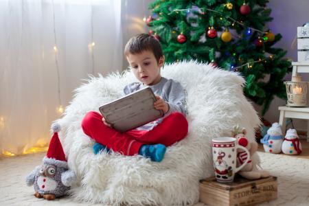 新年树上,一个小男孩正坐在柔软的扶手椅上