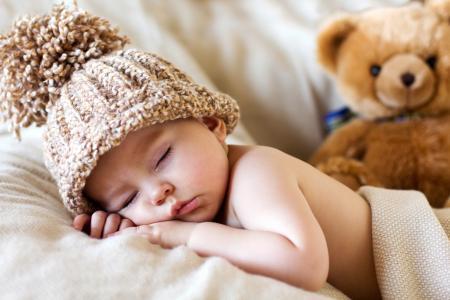 睡觉的婴儿戴着一顶泰迪熊的帽子