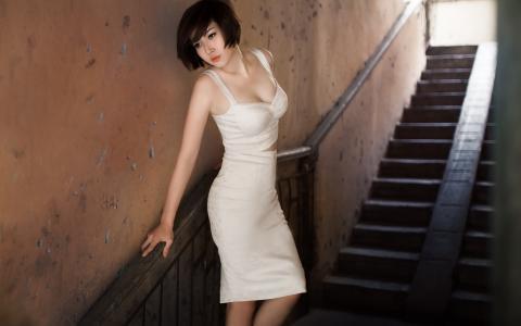 在过渡的楼梯上的白色连衣裙的女孩