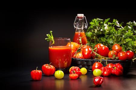 番茄汁和新鲜的西红柿,在黑色的背景上的桌子上
