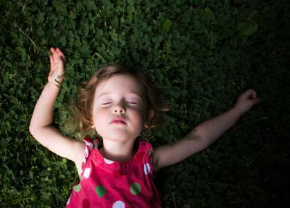 小女孩在绿色的草地上睡觉