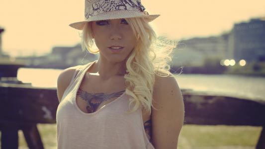 在她的乳房纹身的白色帽子的金发女郎