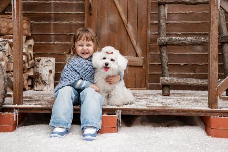 小女孩微笑着坐在一个房子的门廊上的白色狮子狗在冬天