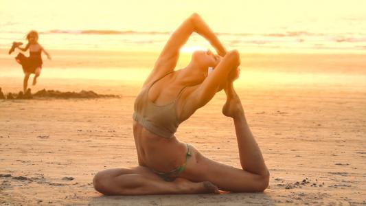 日落海滩上的瑜伽