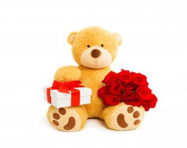 与一束红玫瑰和一件礼物的大泰迪熊