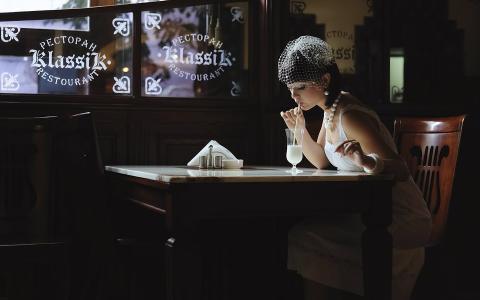 一个穿白裙子的女孩在一家餐馆喝鸡尾酒