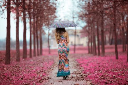 穿着漂亮衣服的雨伞下的女孩沿着胡同走