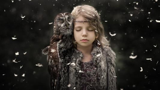 闭着眼睛的小女孩与在她的肩膀的一只猫头鹰