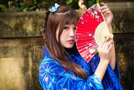 美丽的亚洲女孩,在手中的风扇