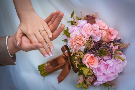 一对恩爱的夫妻与新娘花束的手