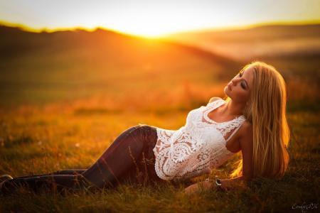模型在摆在日落的牛仔裤