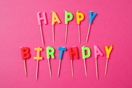 节日蜡烛与题字生日快乐在粉红色的背景上