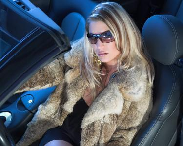 一个穿皮大衣的女孩坐在车里