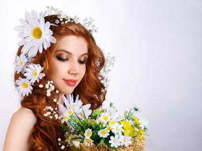 漂亮的红发女孩与花在她的头发