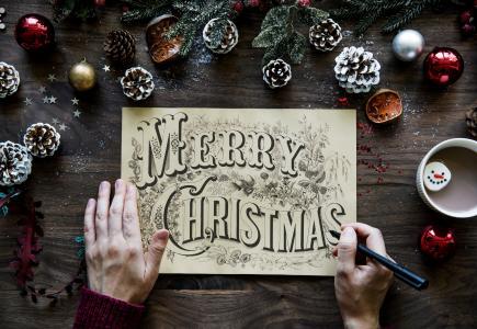 与题字圣诞快乐在圣诞节装饰的桌上的图画