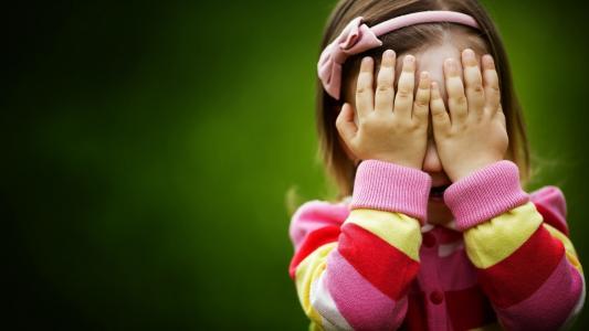甜美的女孩用她的手覆盖她的脸