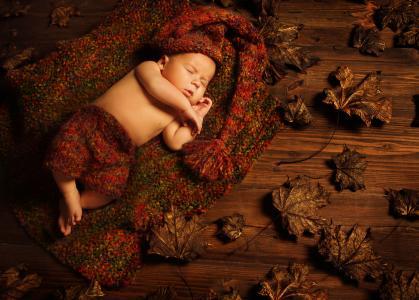 一个小孩子睡在地板上的干燥叶子针织西装