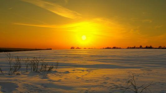 太阳落在白雪覆盖的田野上落在日落