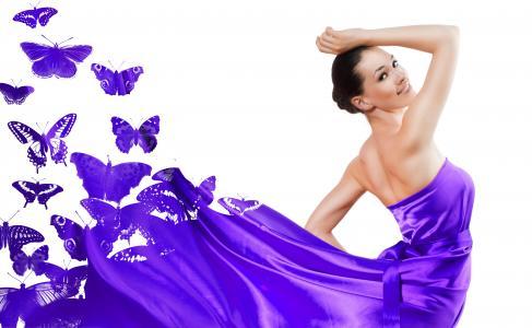 紫色的裙子,在白色背景上的蝴蝶的漂亮女孩
