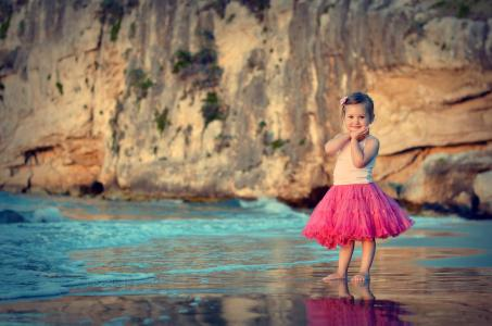 美丽的粉红色裙子,在海滩上的小女孩