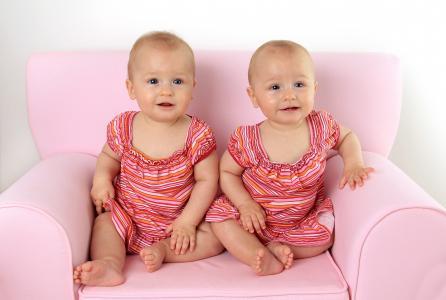 两个可爱的小女孩坐在粉红色的沙发上