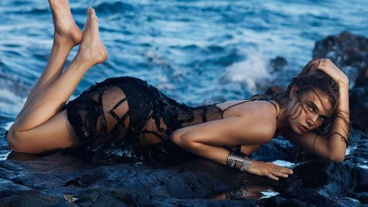 年轻的女演员卡拉·德尔文(Kara Delevin)躺在海边的潮湿的石头上