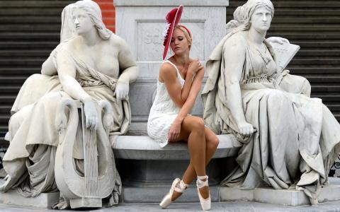 一个女孩在雕像之间的大理石长凳上