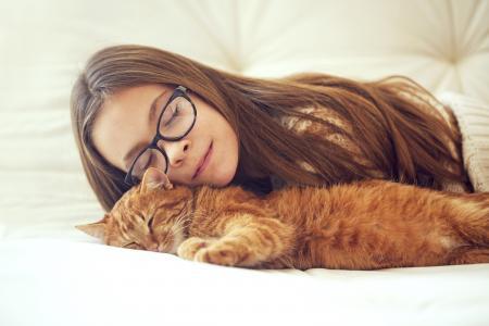 眼镜的女孩睡着一只红色的猫