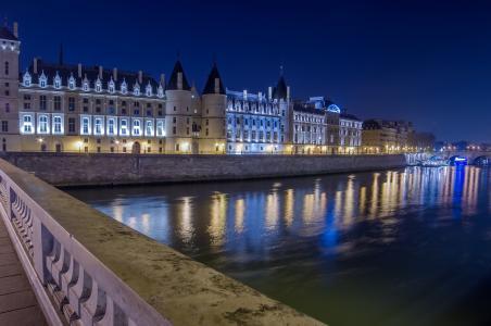 Conciergerie城堡在河里,巴黎的夜晚灯光。