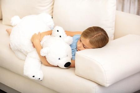 小女孩睡在沙发上的白色泰迪熊
