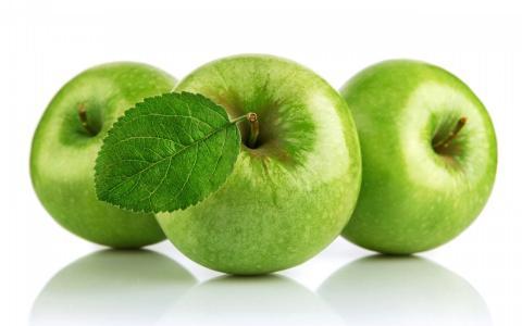 在白色背景上的三个绿色苹果