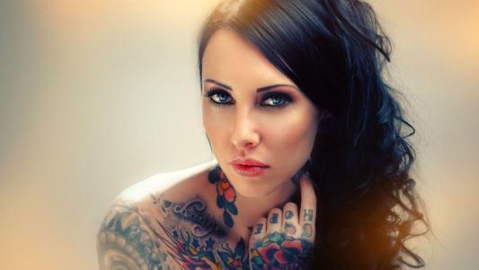 她的手臂和肩膀上的纹身蓝眼睛的女孩