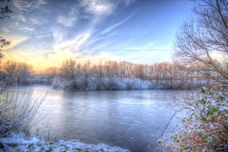在美丽的冬天天空下的森林里的冰冻的河