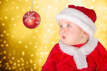 圣诞老人服装的小男婴看圣诞球