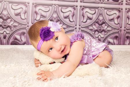 紫色西装的美丽的小女孩与玩具熊