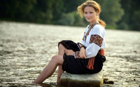 一个女孩坐在传统服装的水边的石头上