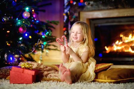 棒棒糖在圣诞树附近的长发金发女孩