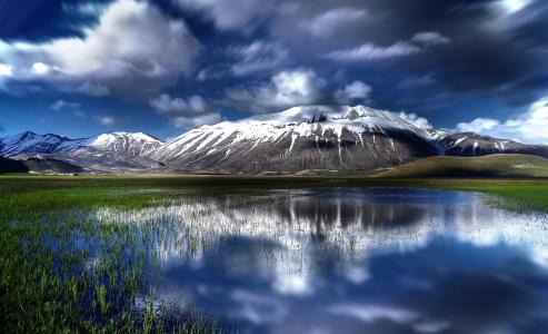 白云倒映在一座高山湖泊的水中