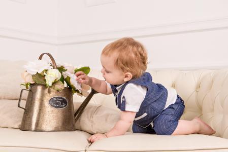 一个年幼的孩子在一个铁壶里检查花朵