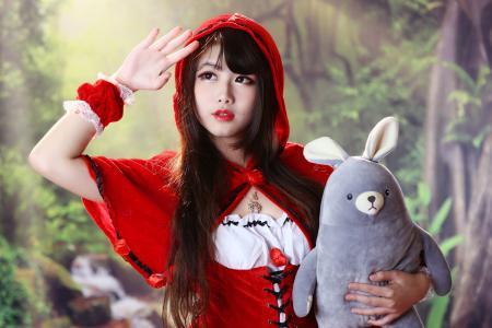 亚洲女孩穿着红色与一个软的玩具