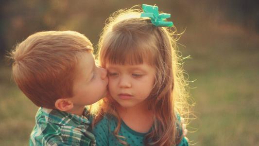 男孩亲吻脸颊上的小妹妹