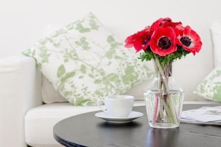 在一个白色杯子的桌子上的花瓶里的红色海葵的花束
