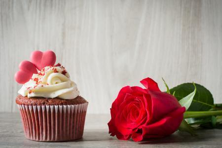 与奶油和红玫瑰在桌子上的蛋糕