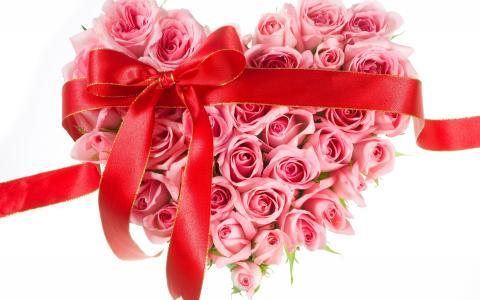 粉红玫瑰的心脏与红丝带在白色背景上